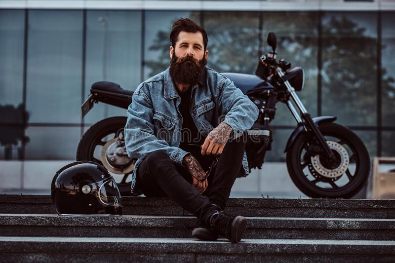 Portrait of a brutal bearded male dressed in a jeans jacket sitting on steps near his custom-made retro motorcycle stock image