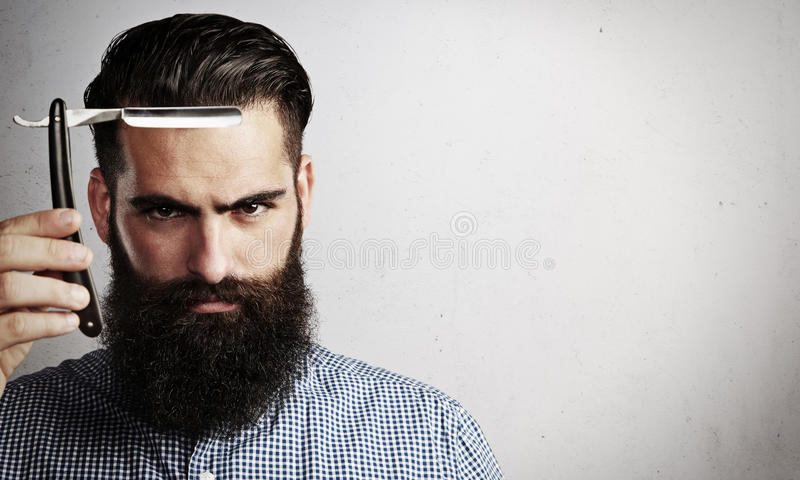 Portrait of brutal man with vintage straight razor royalty free stock image
