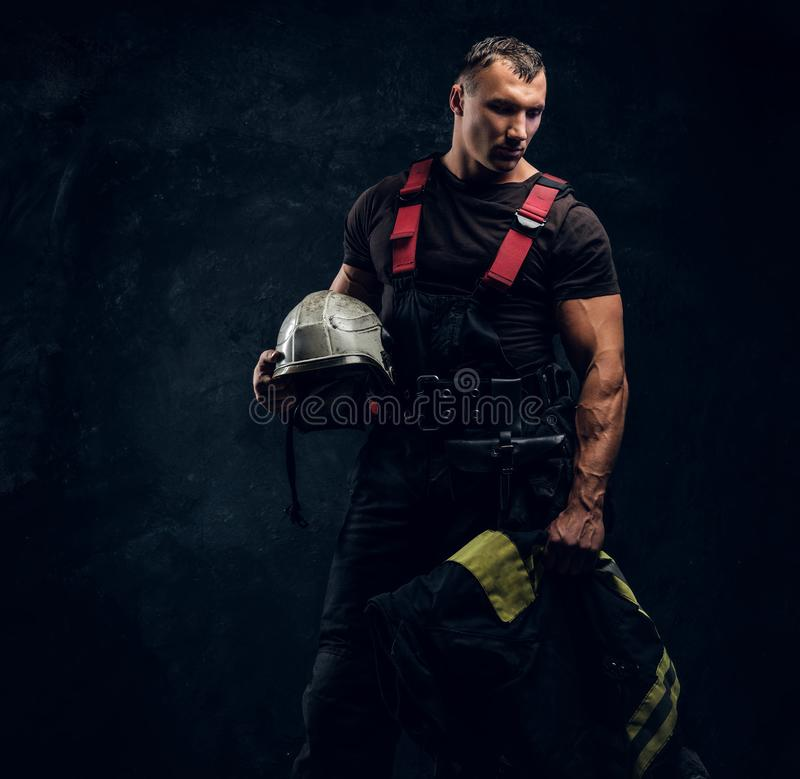 Brutal muscular fireman holding a helmet and jacket standing in the studio against a dark textured wall royalty free stock images