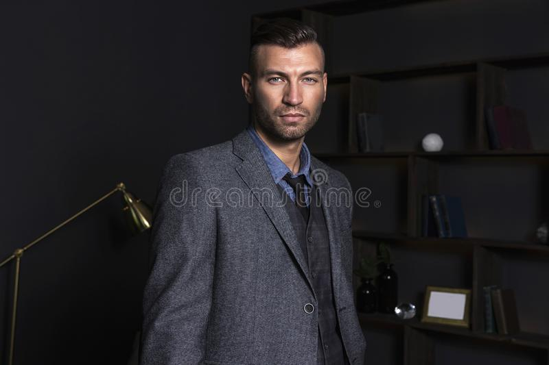 Portrait of a brutal stylish man in a business suit. Elegant handsome man in the house. stock image