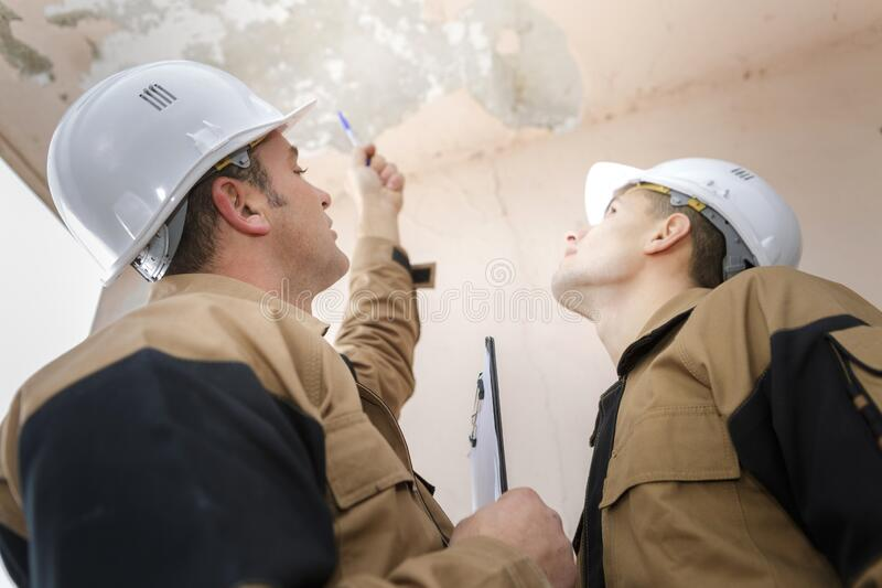 Portrait builders inspecting roof damage royalty free stock images