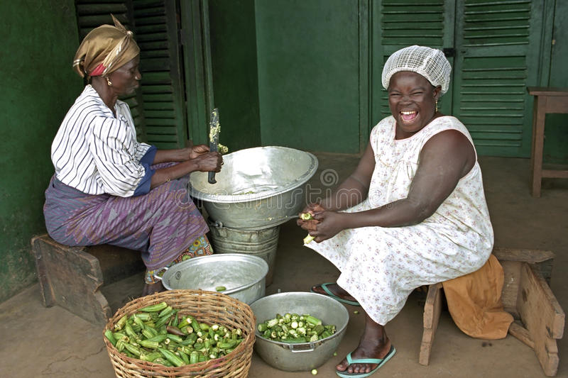 Portrait of burst of laughter Ghanaian cook. Ghana, village Savelugu: Group Portrait [full-length, red carpet] of Ghanaian women, who are busy cutting vegetable stock photos