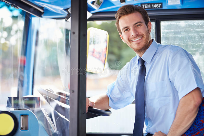 Portrait Of Bus Driver Behind Wheel. Looking To Camera Smiling royalty free stock photography