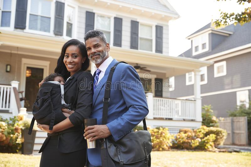 Portrait Of Business Couple With Baby Son Leaving House For Work stock photography