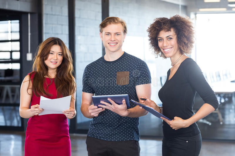 Portrait of business executives standing together in office. Portrait of business executives standing together and smiling in office stock images