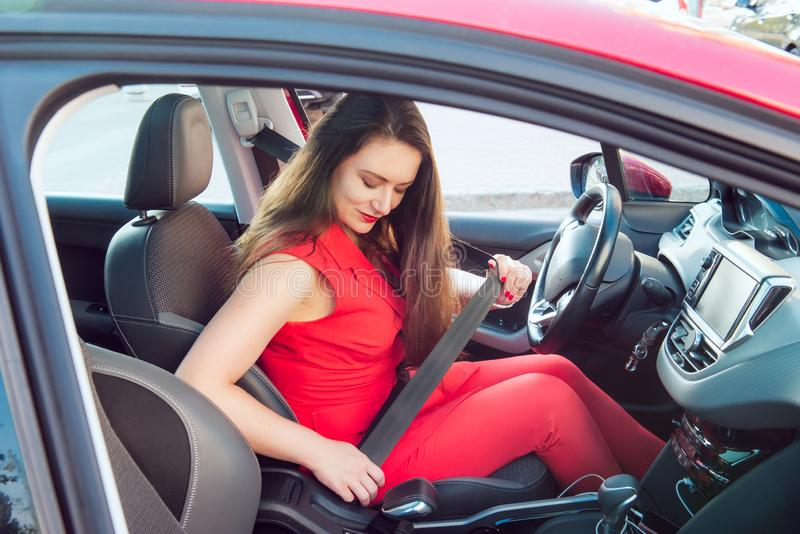 Portrait of business lady, caucasian young woman driver in red summer suit fastening car seat belt while sitting behind the wheel stock photo