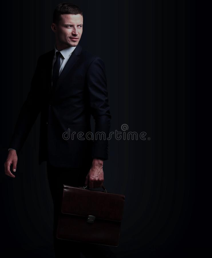 Portrait of a business man with briefcase isolated on black bac royalty free stock photo