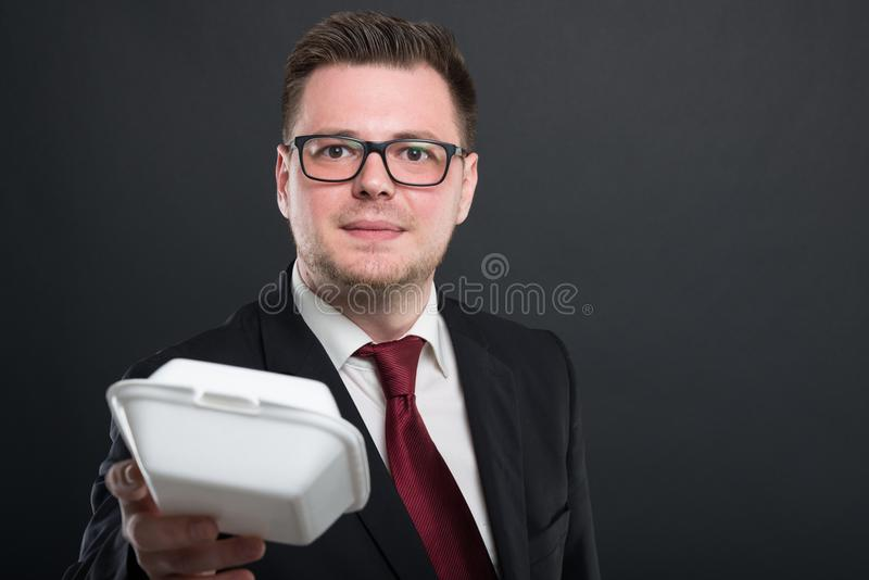 Portrait of business man handing lunch box royalty free stock photography