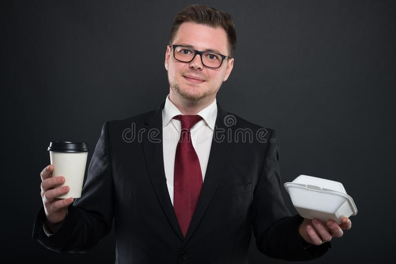 Portrait of business man holding coffee and lunchbox stock image