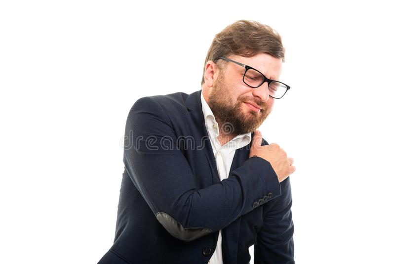 Portrait of business man showing shoulder pain gesture stock photography