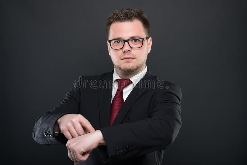 Portrait of business man showing wrist watch. On black background with copypsace advertising area stock photo