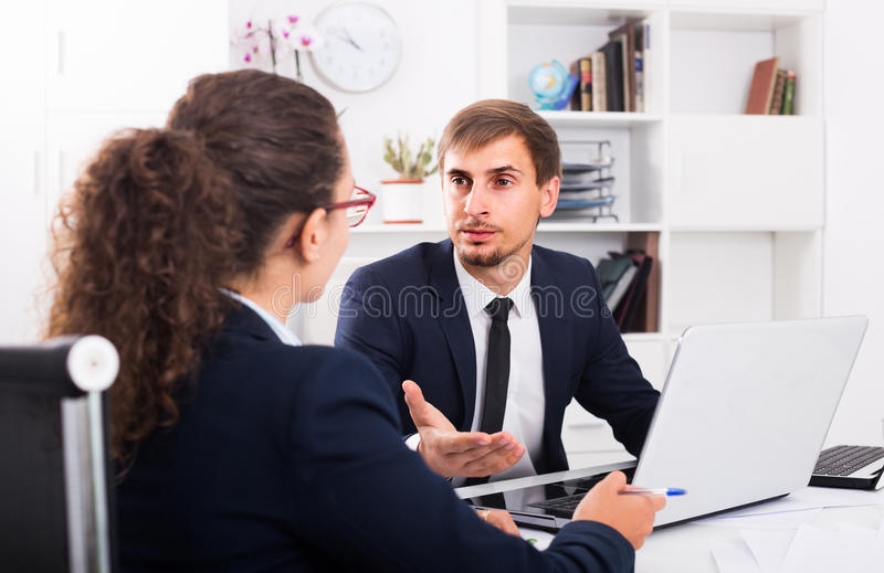 Portrait of business man sitting with computer in office on wor stock photos