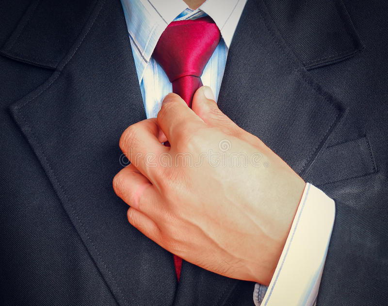 Portrait of business man in suit holding red tie stock images