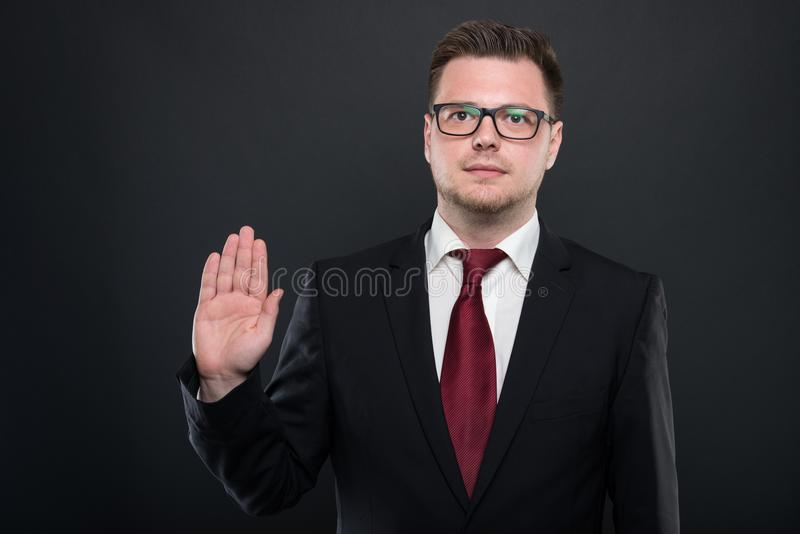 Portrait of business man wearing black suit making oath gesture royalty free stock image