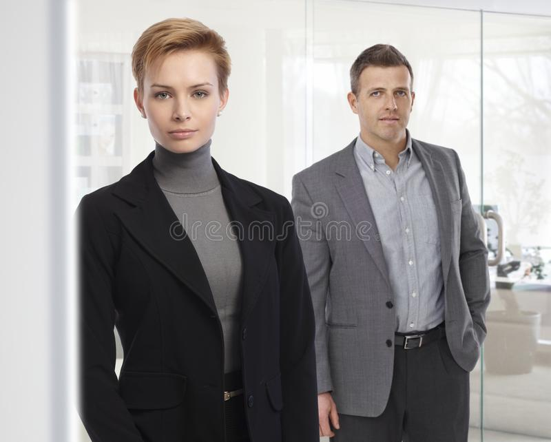 Portrait of business people standing at office. Wearing suit, looking at camera, bright background. Attractive, confident caucasian woman stock photography