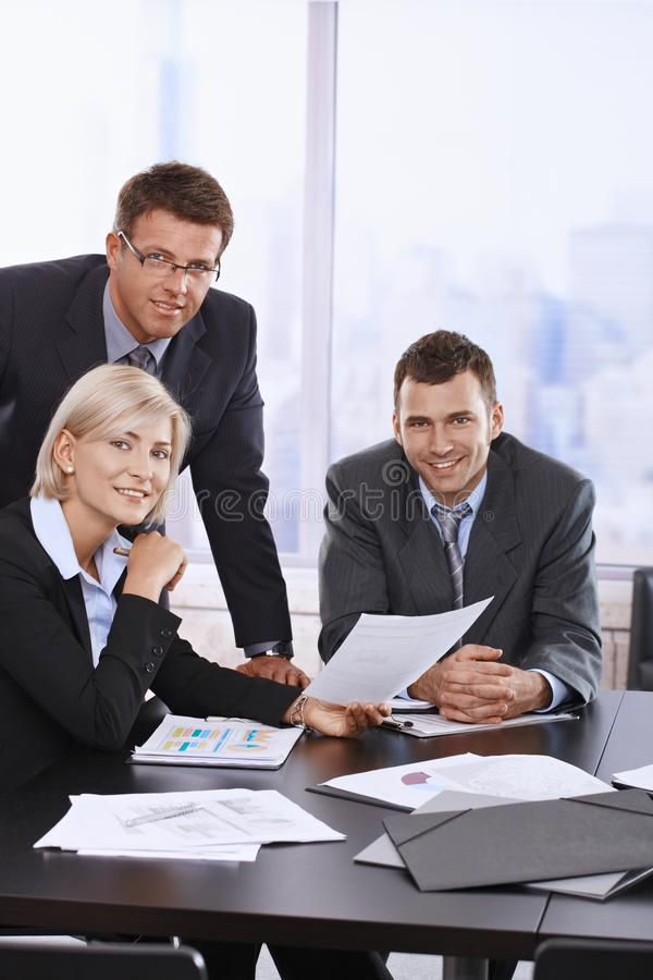 Portrait of business team. Portrait of smiling business team holding document in office royalty free stock photo