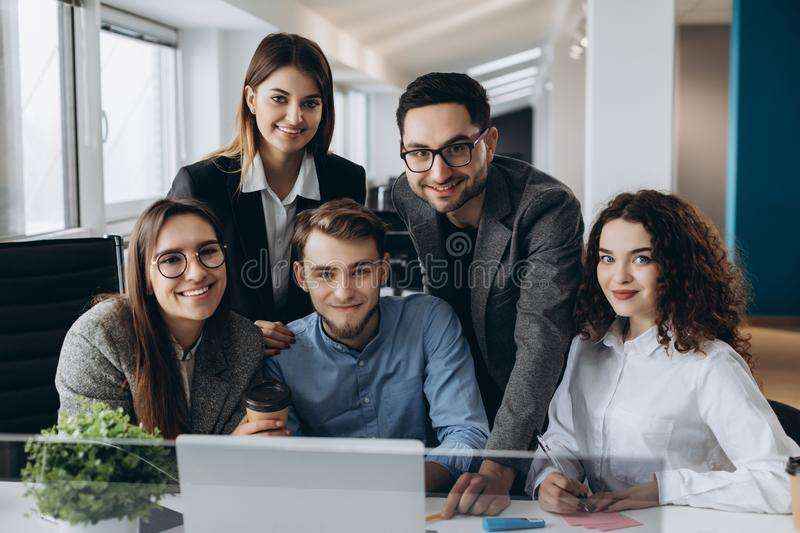 Portrait of business team working together in modern open space office startup. Looking at camera stock photos