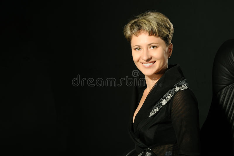 Portrait of the business woman in chair. Portrait of the business woman in a leather armchair. A studio photo on a black background royalty free stock photography