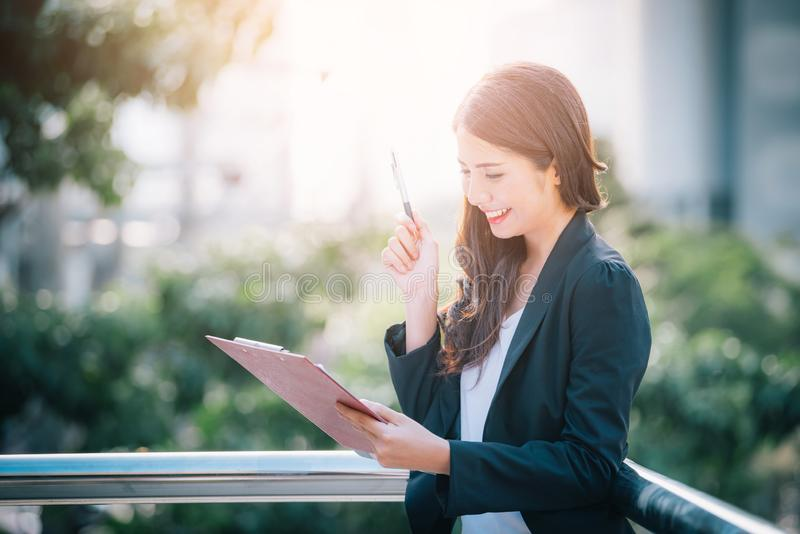 Portrait of business woman happy smile holding check list on clipboard and pen royalty free stock photography