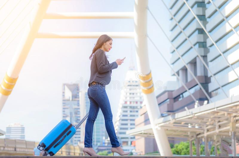 Portrait of business woman looking smartphone with blue travel b royalty free stock photography