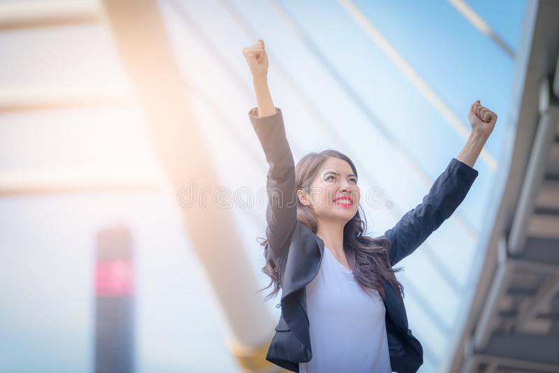 Portrait of business woman smiling with arms up celebrate on blu royalty free stock image