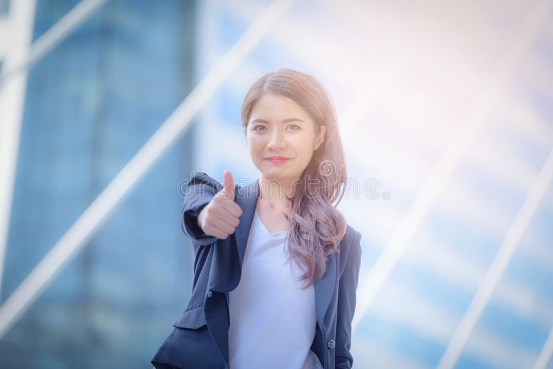 Portrait of business woman smiling and shows thumbs up on blurred city background. Business success concept. royalty free stock photos