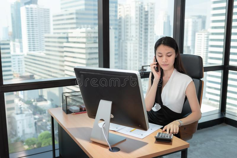Business Woman Using Calculator and Talking on Mobile Phone in Her Office., Beautiful of  Asian Woman is Calling to Someone on Her stock images
