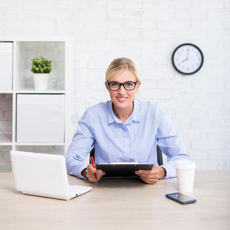 Portrait of business woman sitting in office with computer and c royalty free stock photography