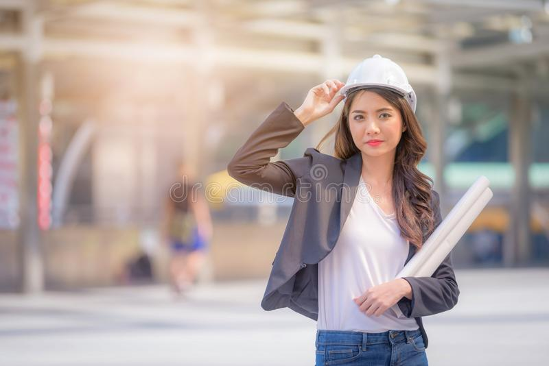 Portrait of Business woman wearing a helmet and holding drawing royalty free stock photo