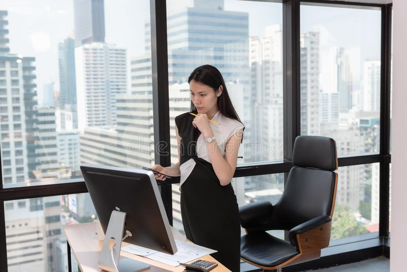 Portrait of Business Woman is Woking on Her Table Desktop in Office Workplace, Attractive Beautiful Businesswoman is Concentrate stock photo