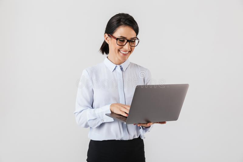 Portrait of businesslike woman wearing eyeglasses holding silver laptop in the office, isolated over white background. Portrait of businesslike woman wearing royalty free stock photos