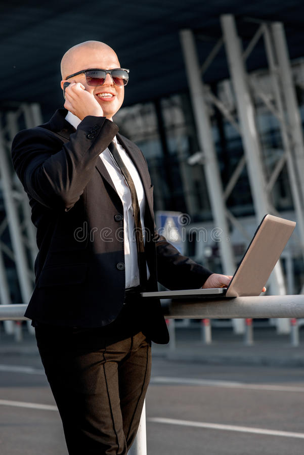 Portrait of businessman. Businessman or banker working with laptop outside the airport or contemporary building stock image