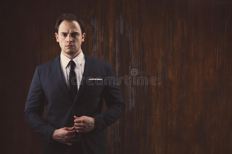 Portrait of a businessman on black red iron background. Portrait of a businessman in a suit on dark red iron background stock images