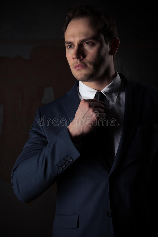 Portrait of a businessman on black red iron background. Portrait of a businessman in a suit on dark red iron background royalty free stock images