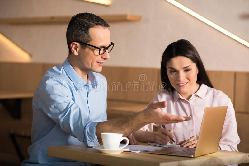 Businessman and businesswoman working in cafe. Portrait of businessman and businesswoman working together in cafe using laptop stock photography