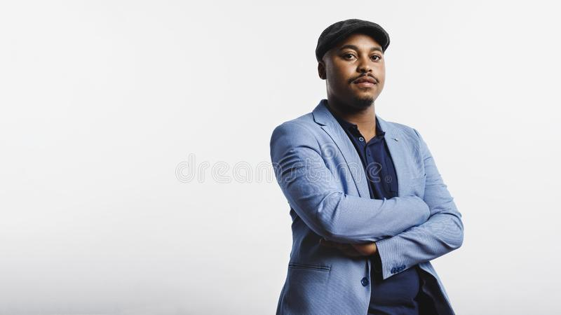 Portrait of a businessman with a cap. African american businessman with arms crossed standing against white background. Man wearing a suit and cap looking at royalty free stock image