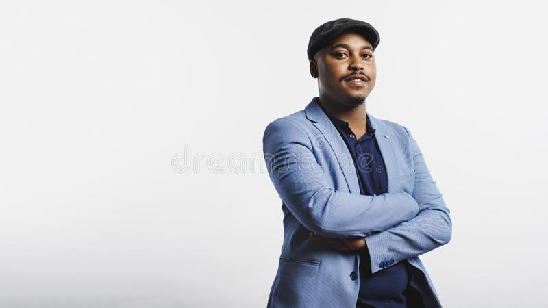 Portrait of businessman in cap. African american man standing against white background with arms crossed. Man wearing a suit and cap looking at camera stock photos