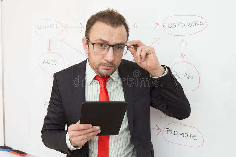 Portrait of a businessman with a digital tablet. Flowchart in the background. Handsome and confident businessman holding digital tablet device. Flowchart on the stock image