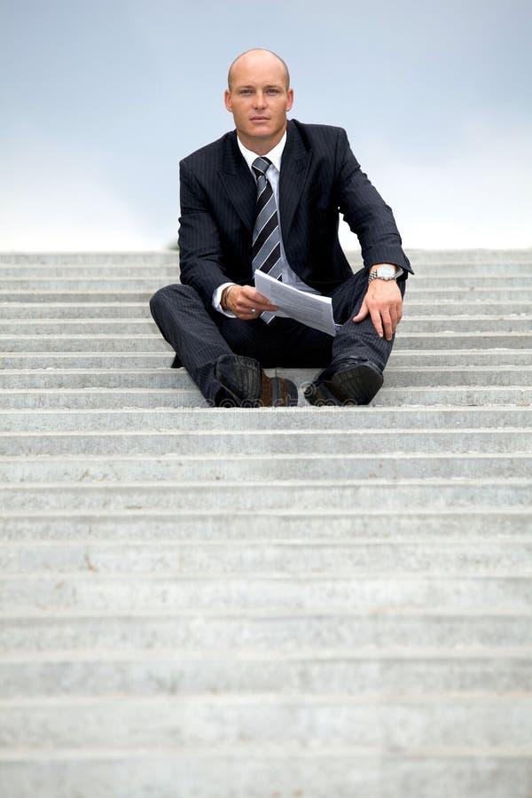Portrait of businessman holding document on steps stock photos