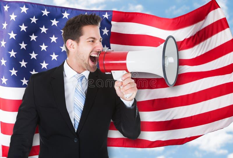 Portrait of a businessman shouting through megaphone stock photos