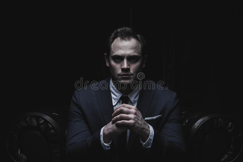 Portrait of a businessman sitting on armchair black background. Portrait of a businessman in a suit on black background stock photo