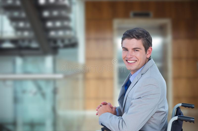 Portrait of businessman sitting on wheelchair in office stock images