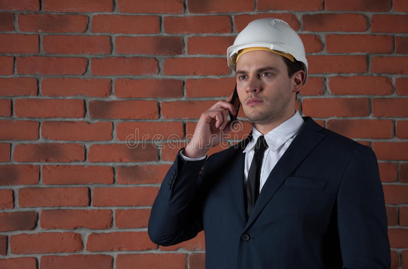 Portrait of a businessman with smartphone in white helmet on red brick wall background. Portrait of a businessman in a helmet with phone in a suit on red brick royalty free stock image