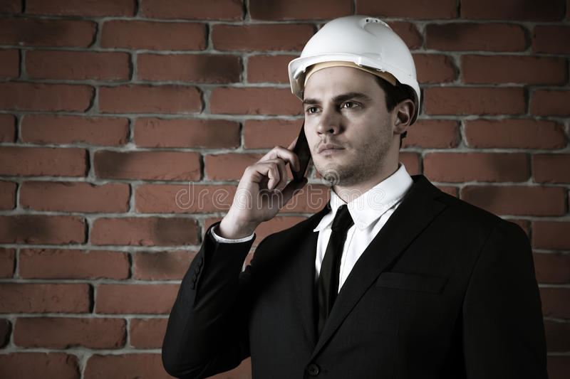 Portrait of a businessman with smartphone in white helmet on red brick wall background. Portrait of a businessman in a helmet with phone in a suit on red brick stock image