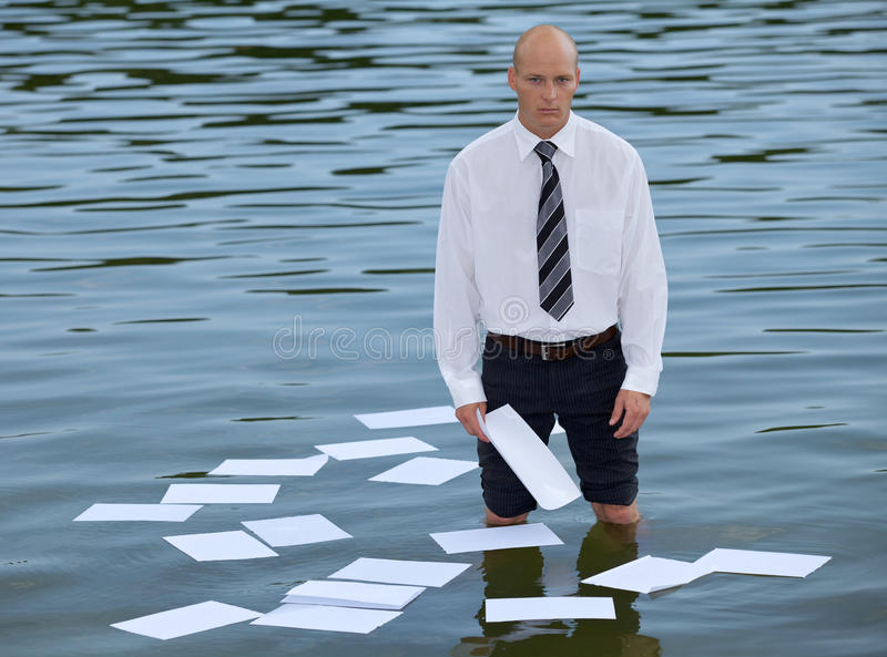 Portrait of businessman standing in lake with papers floating on water royalty free stock image