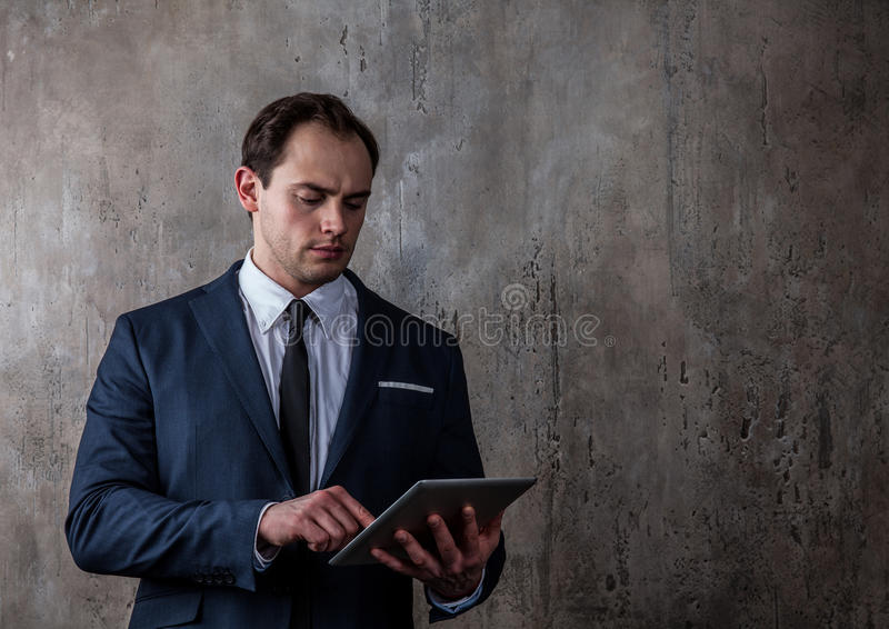 Portrait of a businessman with tablet on concrete gray wall background. Portrait of a mature businessman with tablet in a suit on concrete gray wall background royalty free stock photo