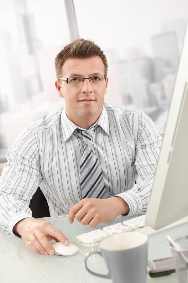 Portrait of businessman using desktop computer stock photo