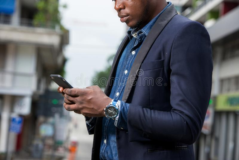 Portrait of businessman using a mobile phone. Businessman using mobile phone application outside office in urban city with skyscrapers buildings in the stock photo