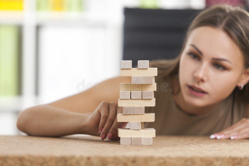 Portrait of businesswoman building a tower. Centered girl in beige is building a tower from wooden bricks at her workplace in a white office. Concept of a break stock photos