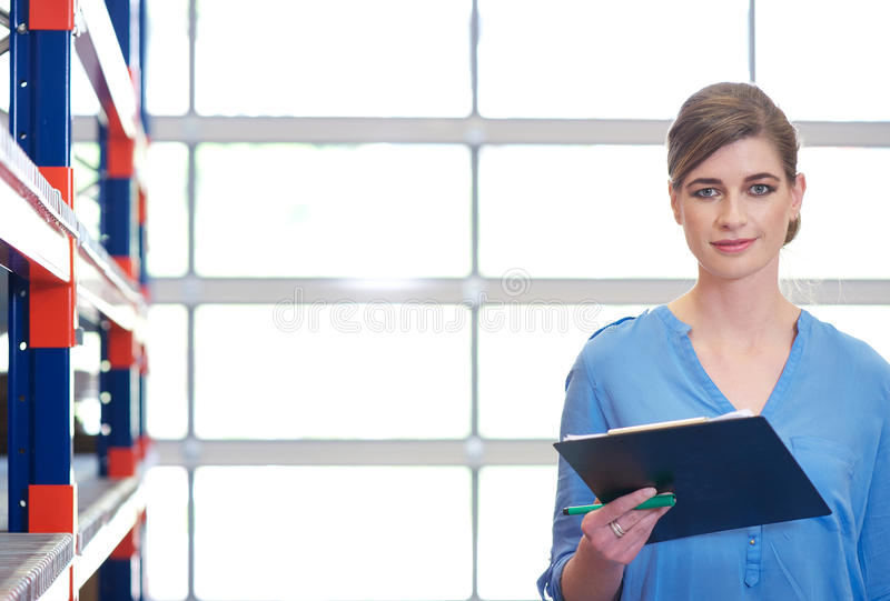 Portrait of a businesswoman with clipboard in warehouse stock photo